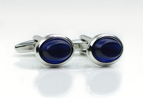 Oval shaped cufflinks with blue glass inlay